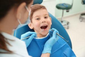 niño sonriendo en la silla dental